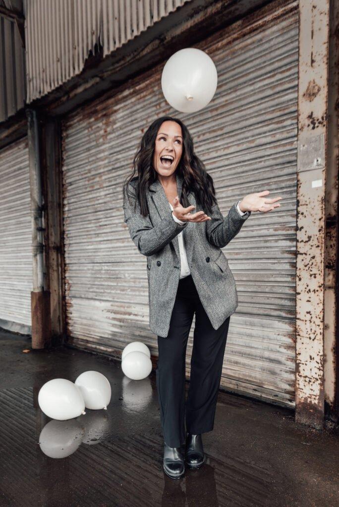 Glad tjej i en industribyggnad som kastar ballonger