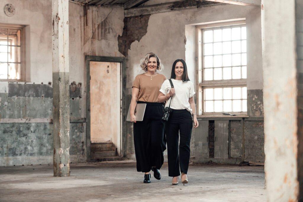 Frendberg Agency. Jessica och Sofia går mot kameran i en industrilokal