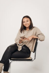 Studiofotografering frendberg akademi med Frendberg Agency blogg. Mathilda sitter på en stol och håller i en telefon och har svart och beiga kläder.