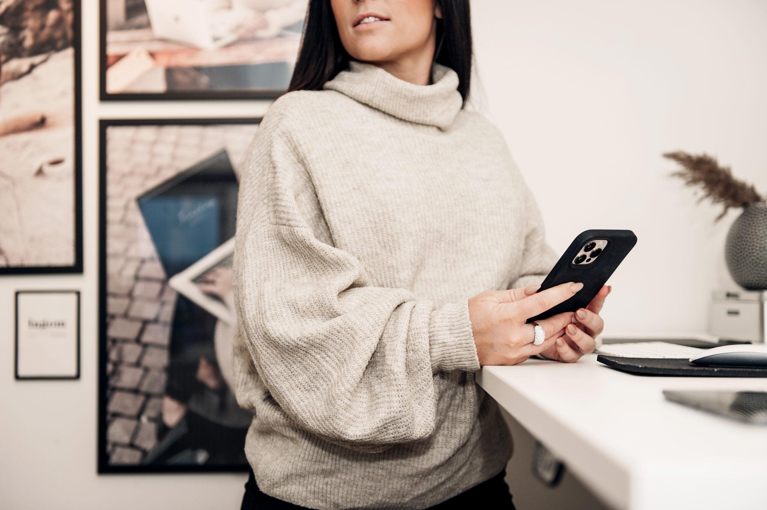 Jessica Frendberg står vid bordet med sin telefon